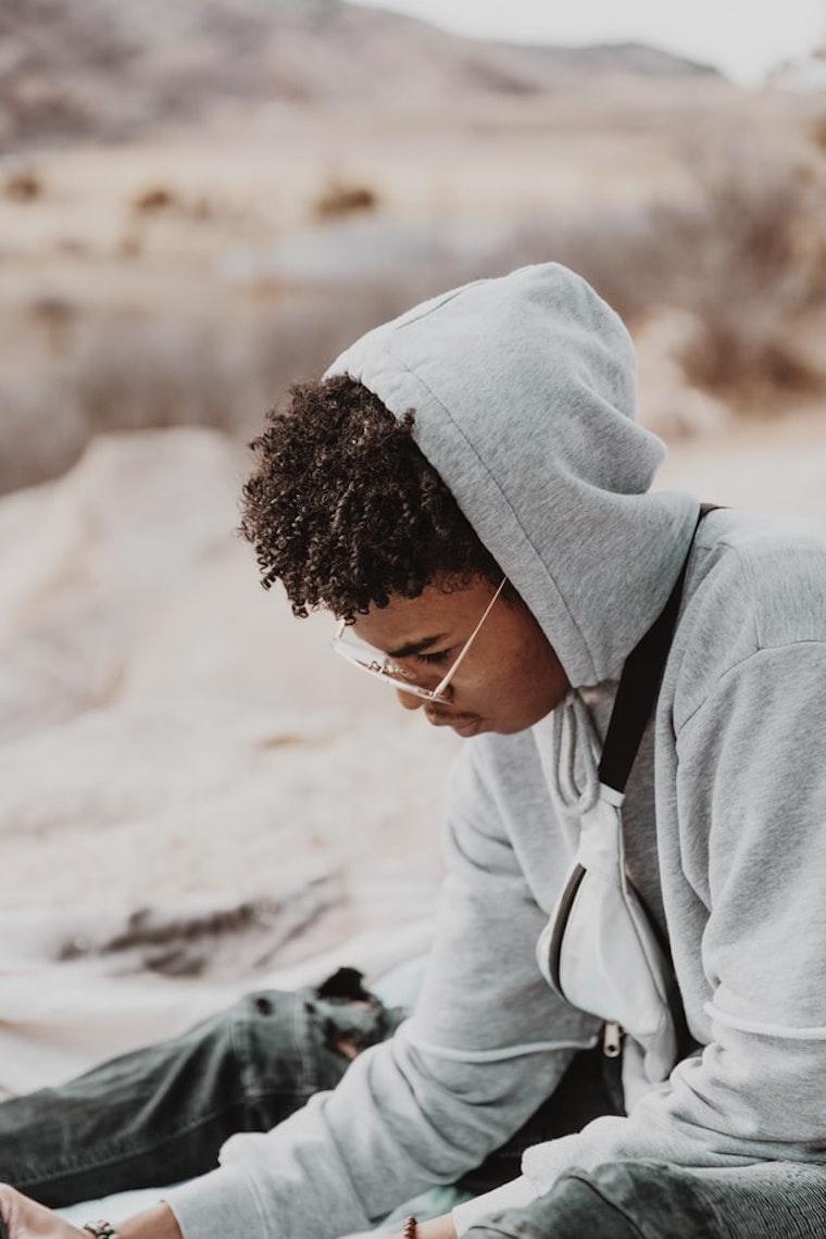 grigio felpa con cappuccio maschio ragazzo seduto sulla spiaggia