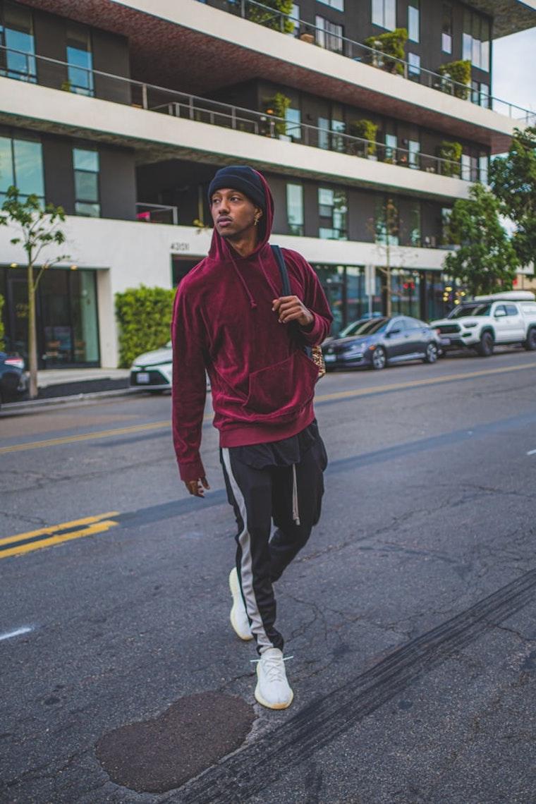 ragazzo alto che attraversa la strada con felpa rossa cappello nero da uomo