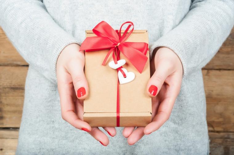 regalo personalizzato per 14 febbraio donna che tiene pacco incartato con fiocco