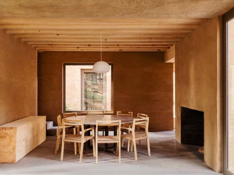 sala da pranzo con tavolo rotondo in leggno pareti dipinti di marrone effetto boiserie
