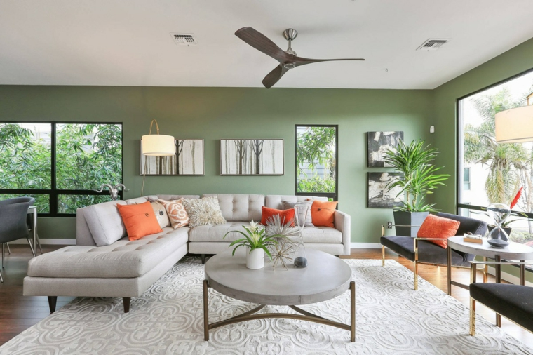 salotto con divano ad l tavolino rotondo con pianta parete dipinte di verde