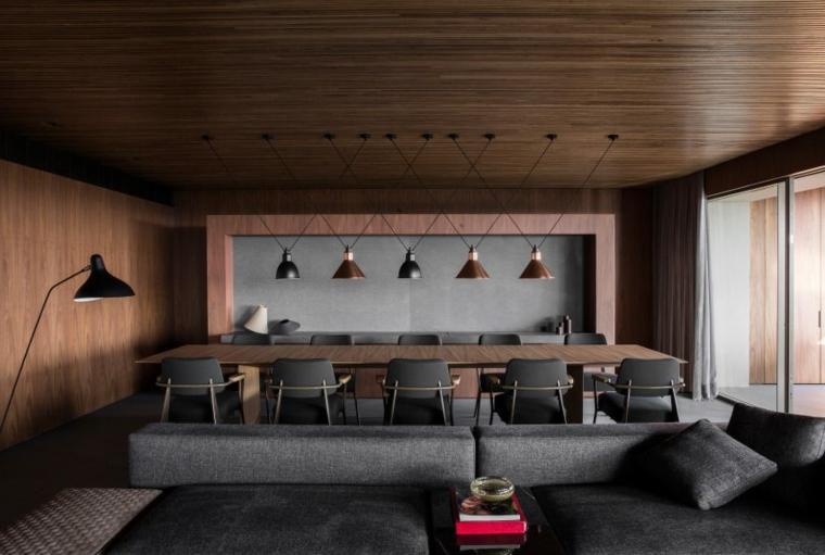 salotto e sala da pranzo insieme divano grigio grande soffitto e parete in legno scuro