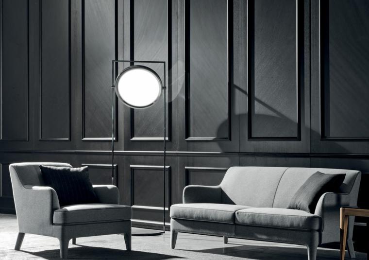 soggiorno con divano e poltrona grigie parete con pannello in legno boiserie