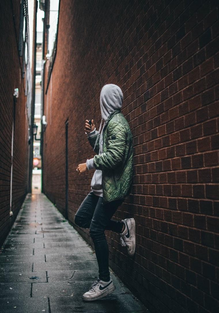 street fashion boy appoggiato su un muro grigio jeans giacca uomo