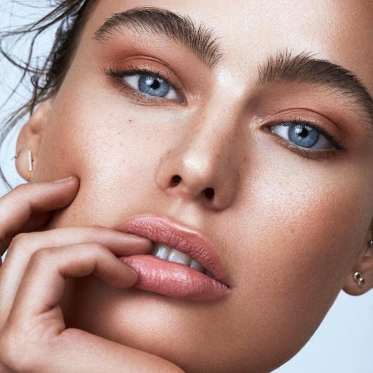 donna con occhi azzurri come infoltire le sopracciglia viso truccato con illuminante