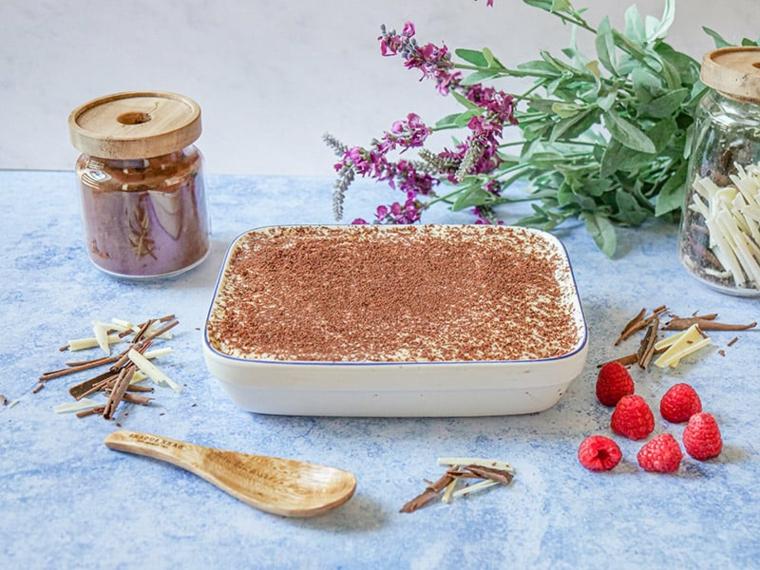 ricetta tiramisù senza uova pirofila di vetro con dolce decorato con cacao in polvere