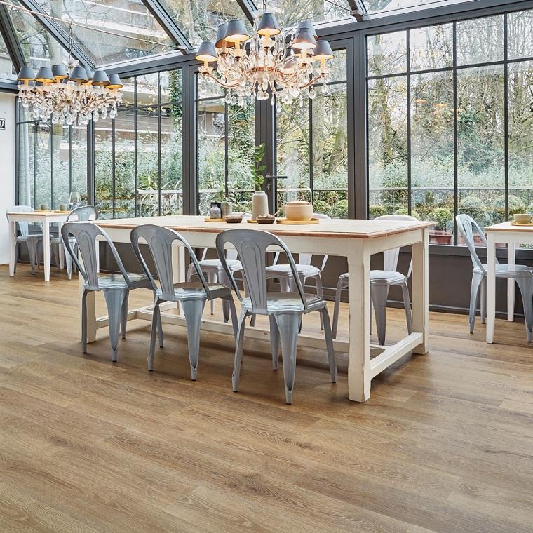 sala da pranzo con grandi vetrate pavimento in pvc di colore chiaro