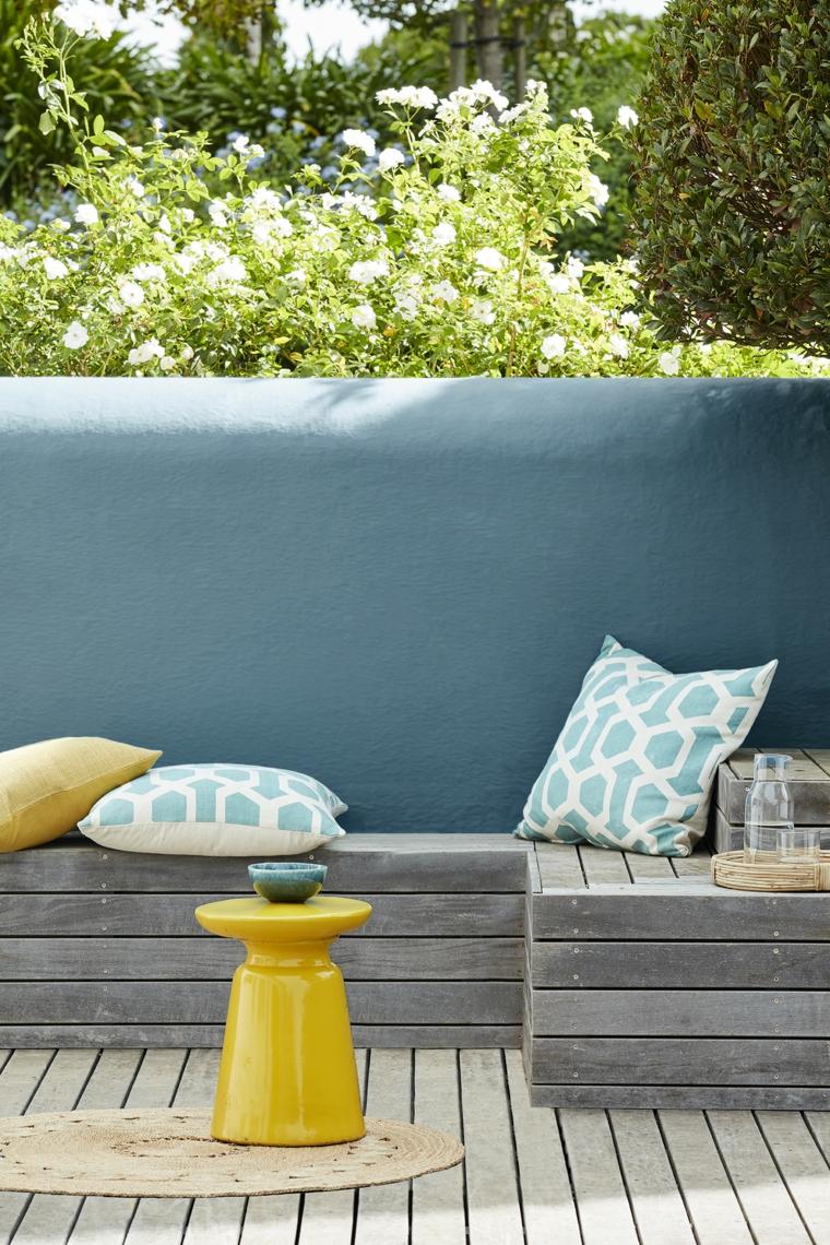 come arredare un giardino piccolo panchina in legno e tavolino in plastica giallo