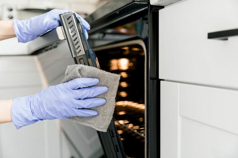 come pulire il forno con limone e bicarbonato donna che pulisce porticina di vetro