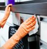 come pulire il forno donna che con panno pulisce gli elettrodomestici in cucina