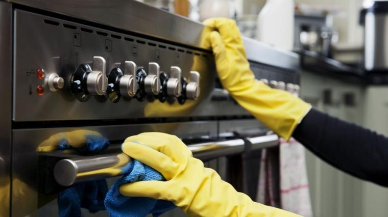 come pulire il vetro del forno con rimedi casalinghi donna che pulisce con guanti di gomma