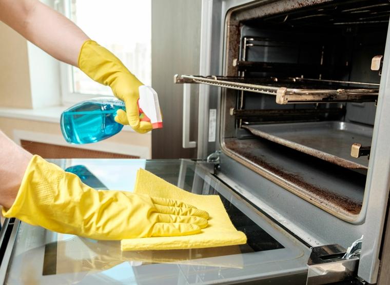 come pulire il vetro del forno donna che pulisce con spruzzino e spugna