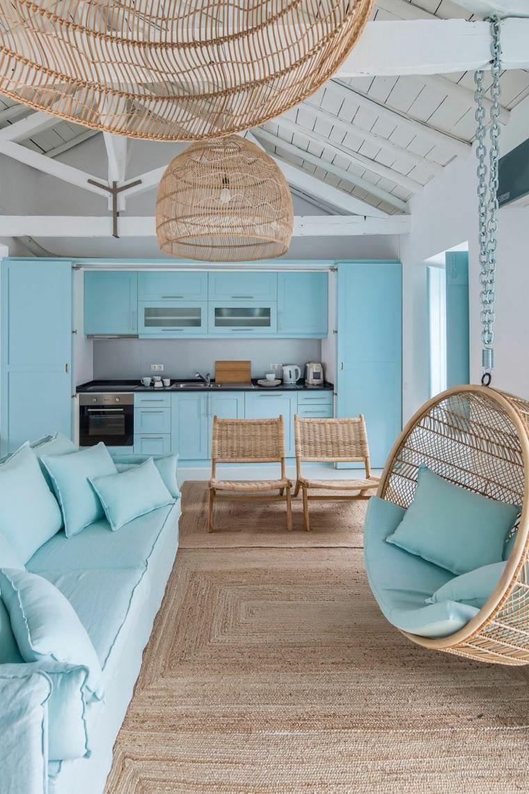 open space con elementi in rattan color tiffany pareti divano con cuscini colorati