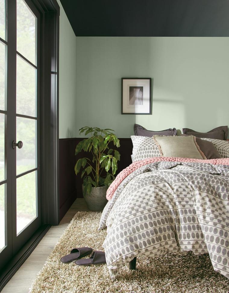 parete di due colori nero e bianco decorazione camera da letto con pianta foglia verde