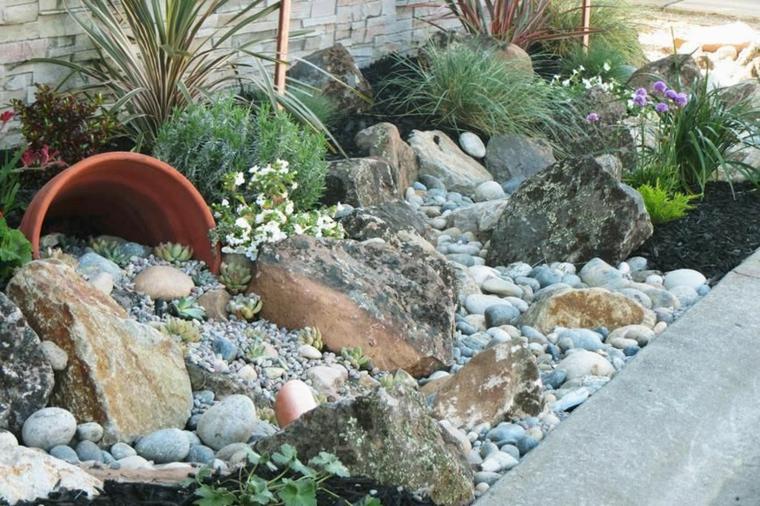 aiuole con sassi e piante perenni decorazione giardino con anfore e rocce
