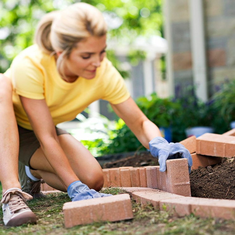 bordure aiuole fai da te donna che sistema il giardino con terriccio e piante