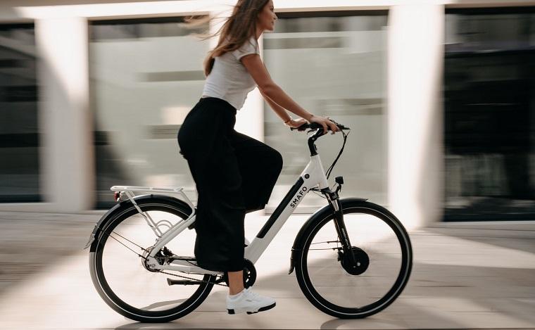 donna che pedala bicicletta elettrica e bike con gomme nere