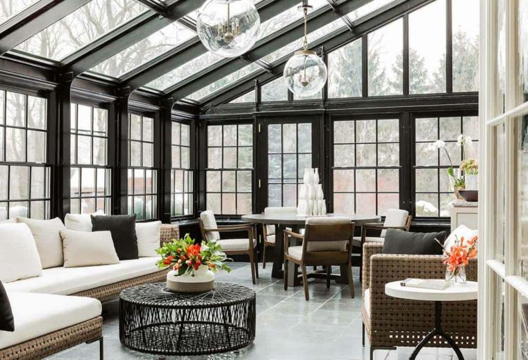 veranda con soffitto in pendenza con vetrate arredo con mobili in rattan