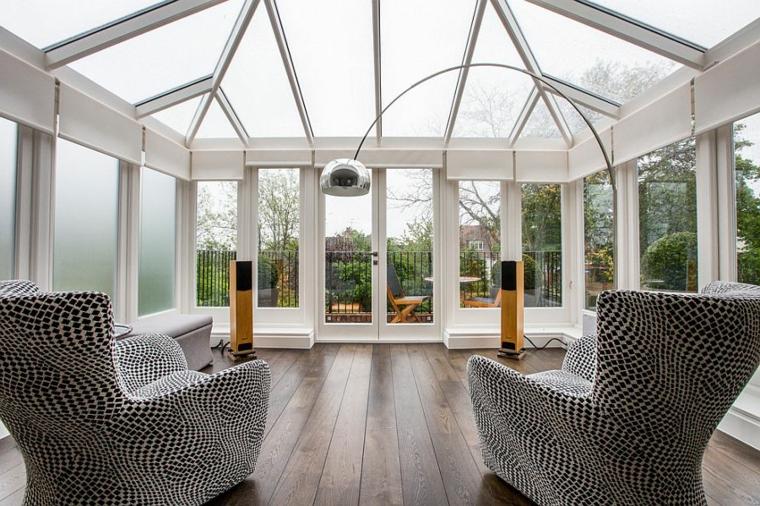 veranda ricoperta in vetrate come arredare un giardino d inverno due poltrone in tessuto