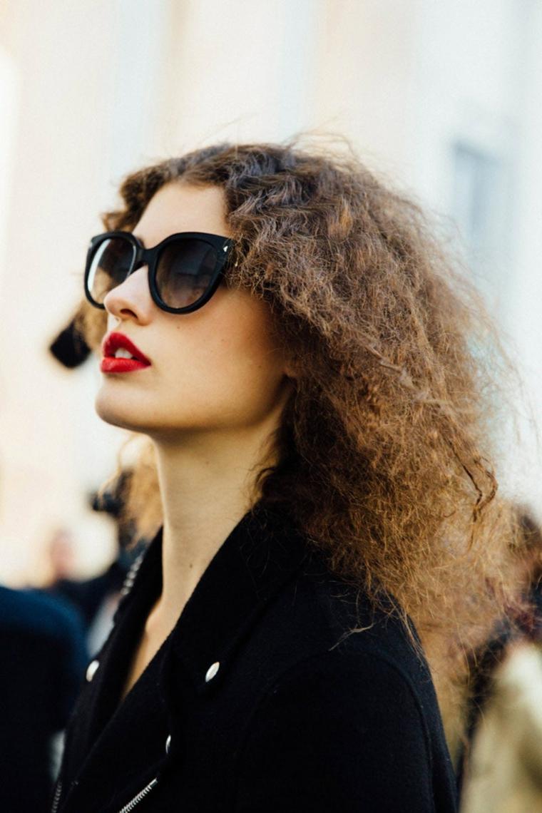 acconciature capelli ricci lunghi donna con rossetto rosso e occhiali da sole