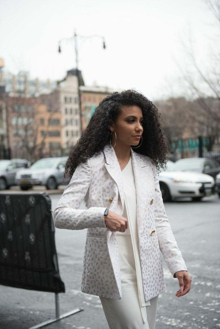 acconciature capelli ricci sciolti donna con cappotto bianco