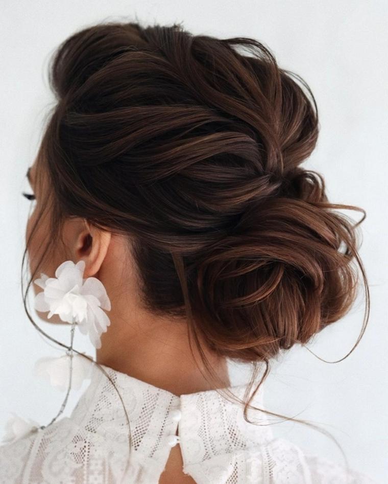 acconciature sposa capelli ricci di colore castano raccolto basso morbido