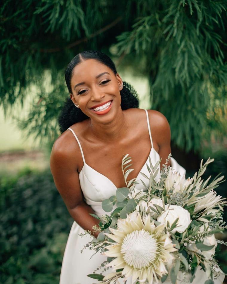 acconciature sposa capelli ricci semiraccolto donna con bouquet di fiori
