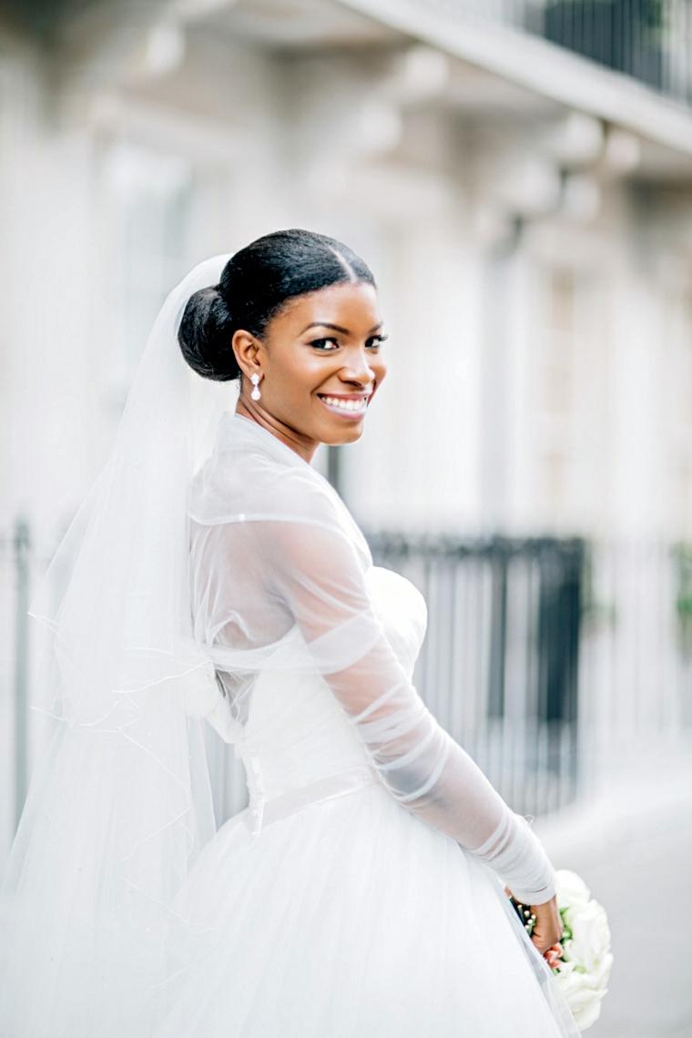 acconciature sposa raccolti donna con capelli legati a chignon basso con velo