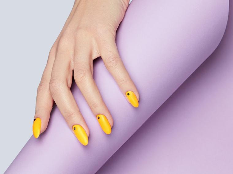 colori smalto estate 2021 manicure a mandorla di colore giallo con puntini neri
