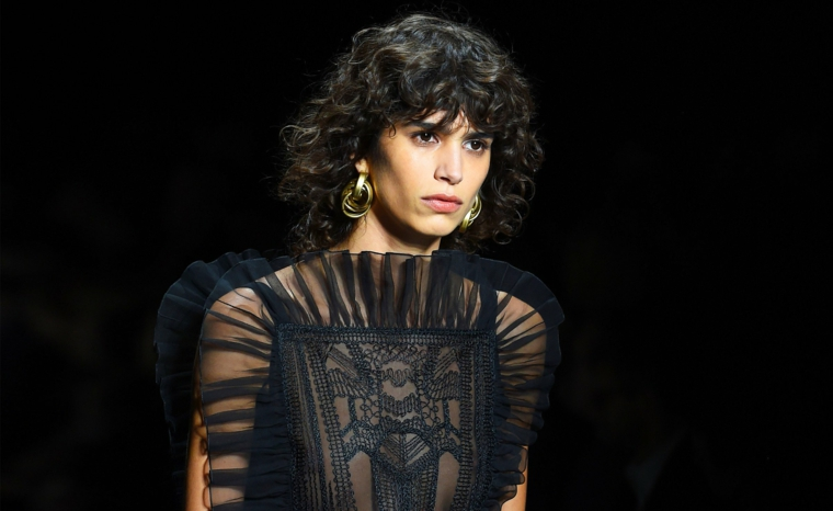 donna con capelli di colore nero taglio shag con frangia riccia