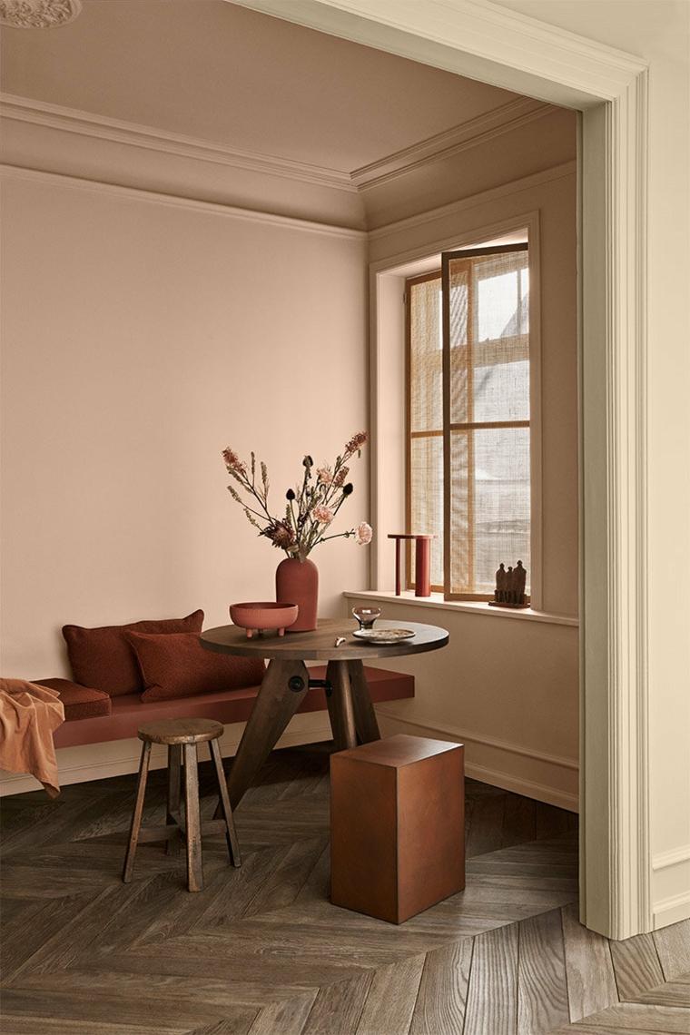 salotto con muro dipinto di tortora arredo con tavolo rotondo e divano