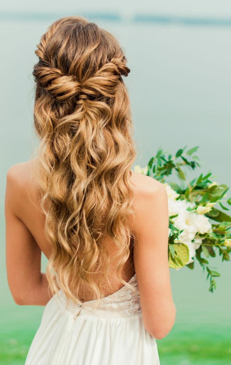 sposa con bouquet in mano capelli biondi con semiraccolto morbido