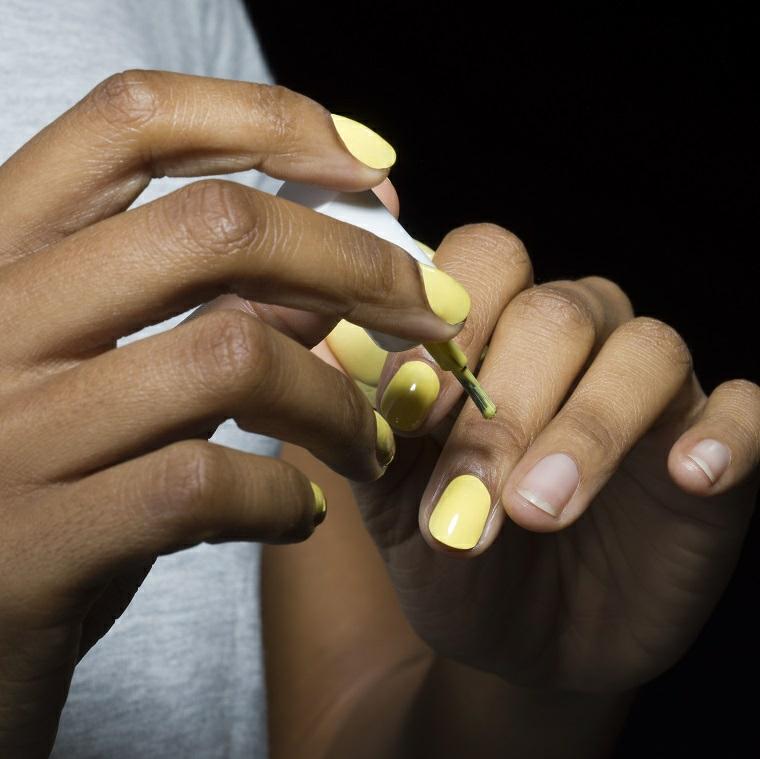 unghie color pastello donna che si mette smalto di colore giallo