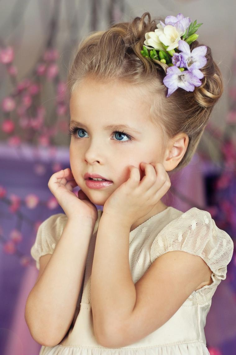 acconciature comunione bambina capelli biondi legati a chignon con fiori
