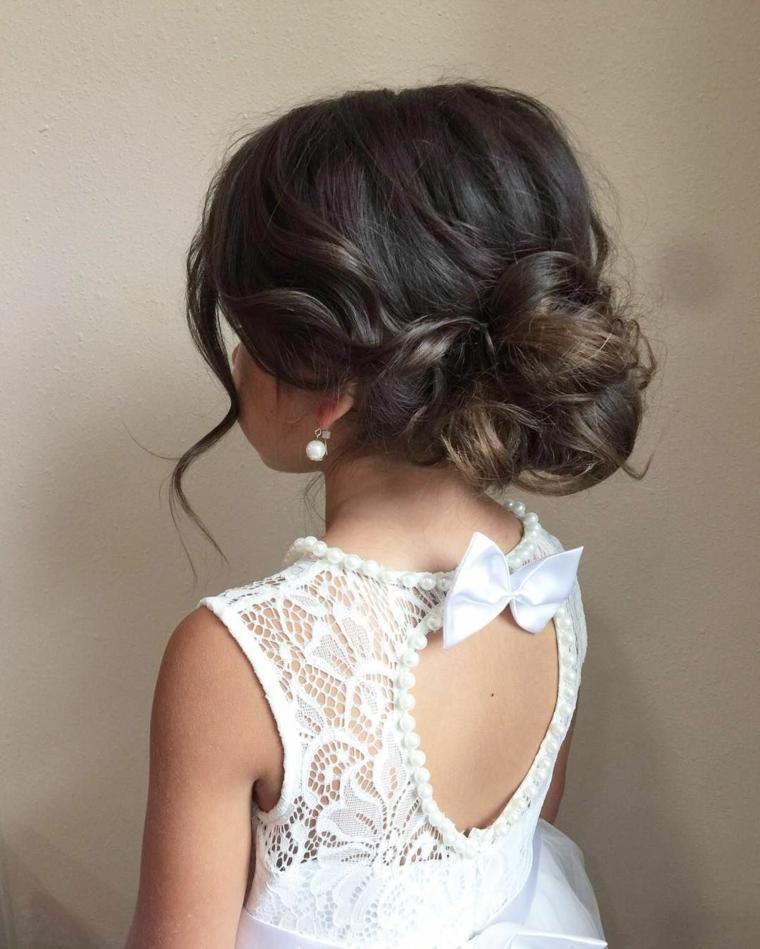 acconciature comunione bambina capelli castani ricci legati a chignon