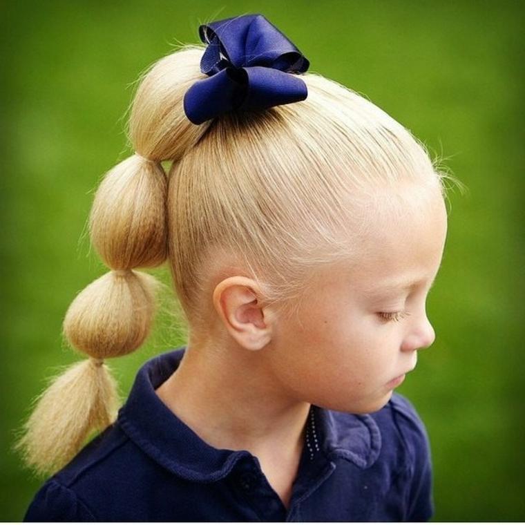 bambina con capelli biondi lunghi acconciatura con coda e fiocco