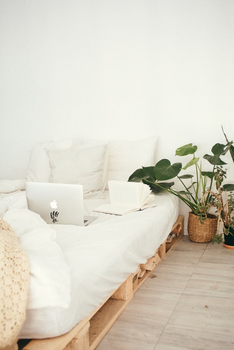 bancale di legno con materasso e cuscini divano con pallet