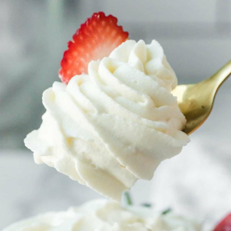 cucchiaio con panna montata di colore bianco fetta di fragola