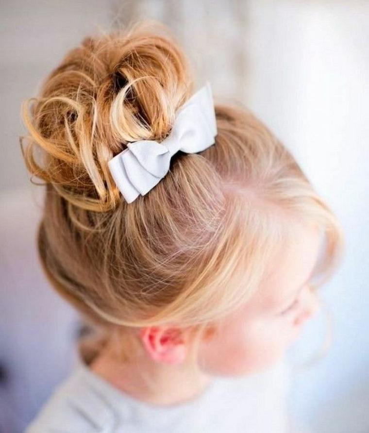 pettinatura capelli biondi acconciature comunione bambina chignon alto