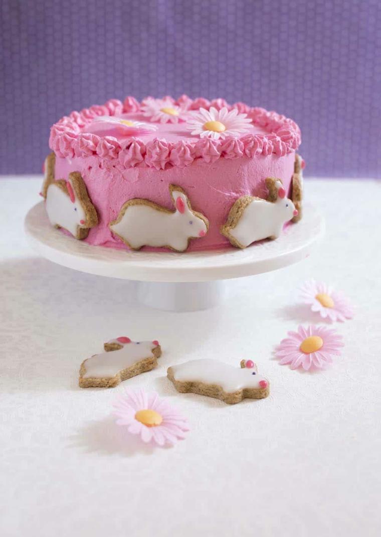 torta di pasqua con panna rosa decorazione con biscotti forma di coniglio