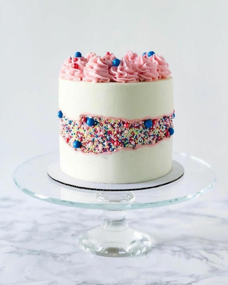 torta rotonda alta con panna di colore rosa decorazione con glassa bianca