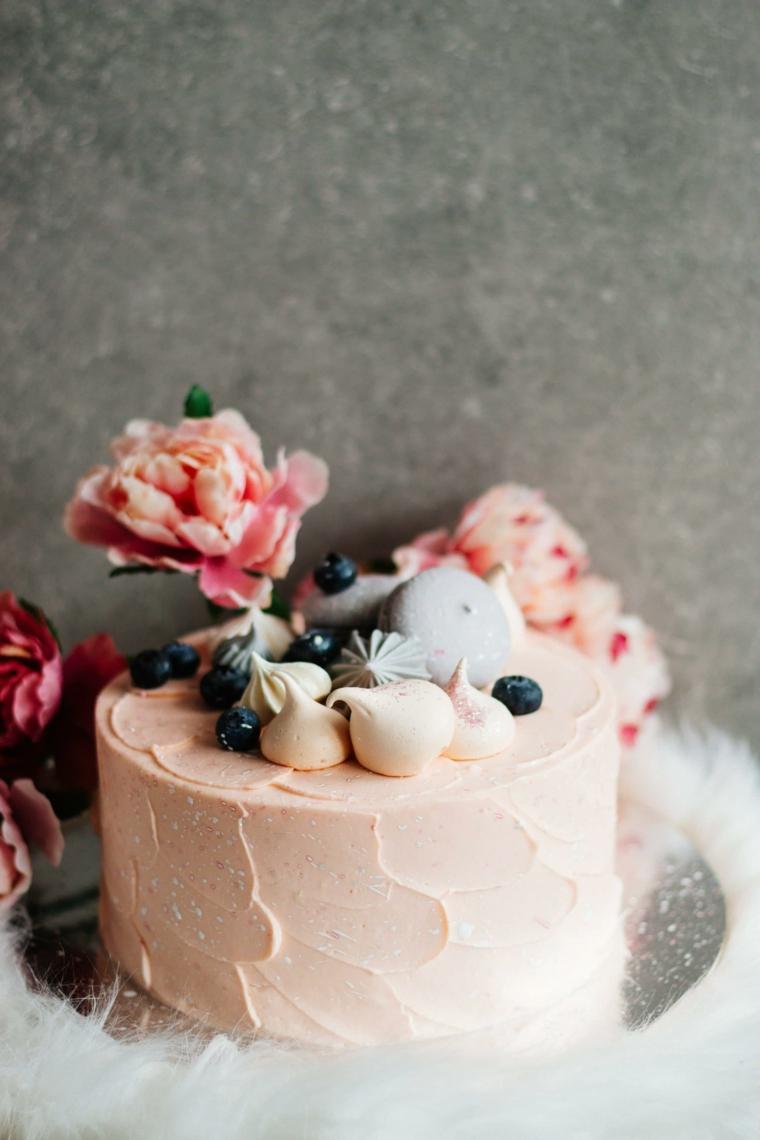 torta rotonda decorata con panna montata di colore rosa decorazione con fiori
