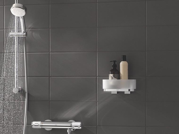 accessori da bagno appesi alla parete bagno con piastrelle nere