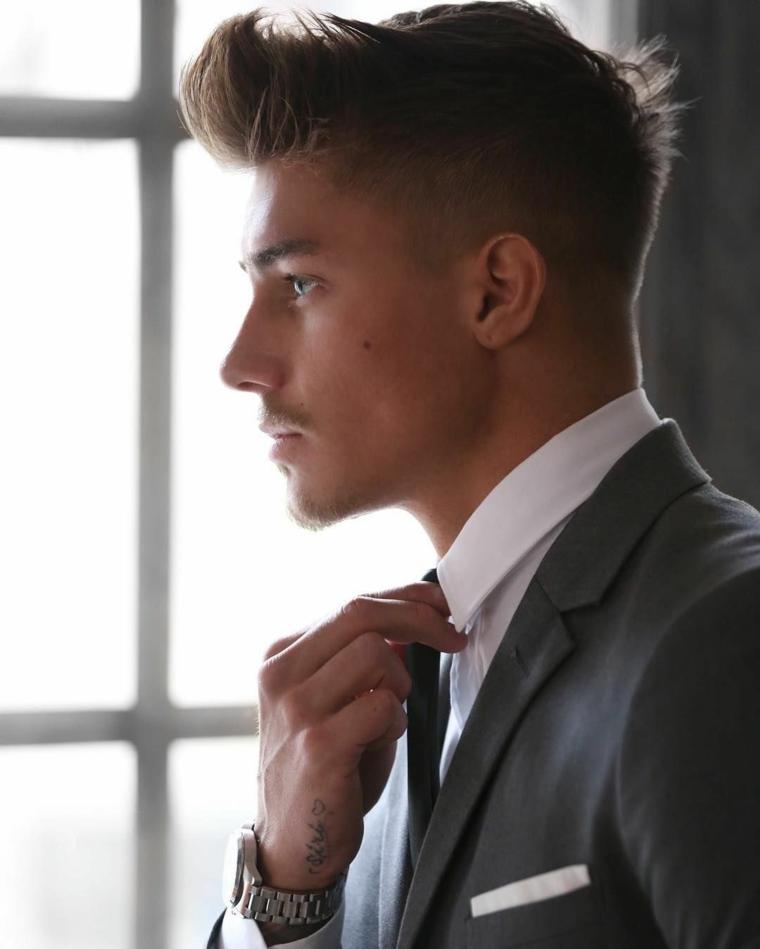 acconciatura uomo rasato ai lati con ciuffo davanti capelli di colore biondo