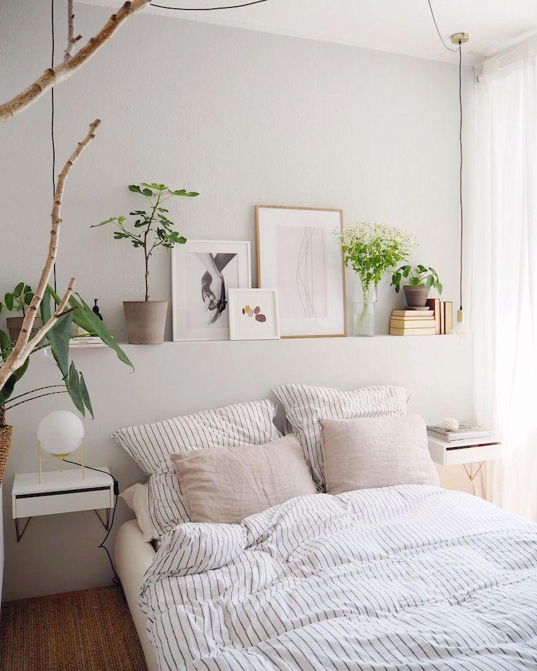 camera da letto bianco e grigia decorazione con quadri e piante