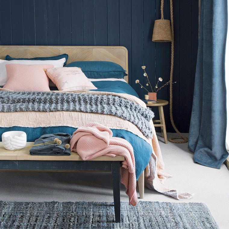 camera da letto con boiserie di legno dipinta di blu abbinamento a rosa