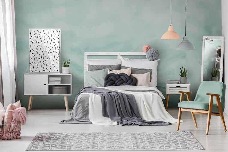 parete dipinta di verde menta testata letto in pallet zona notte nei colori pastello