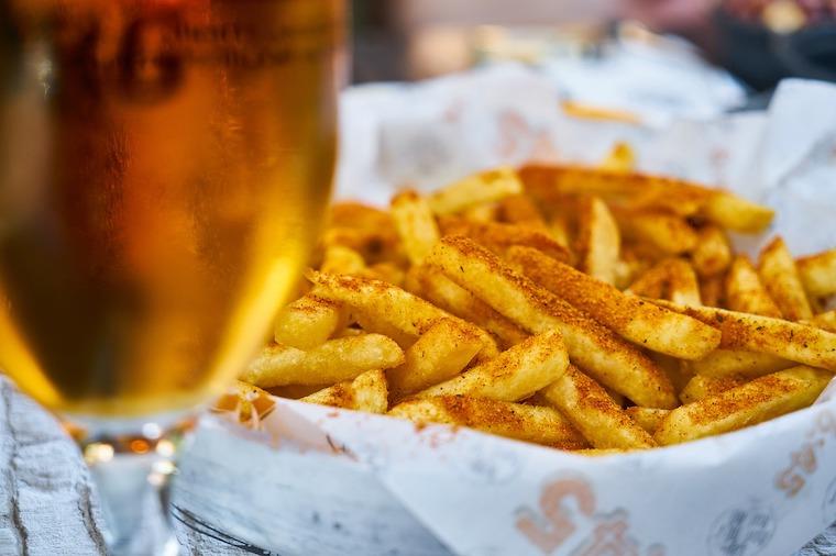 piatto di patatine fritte con bicchiere di birra