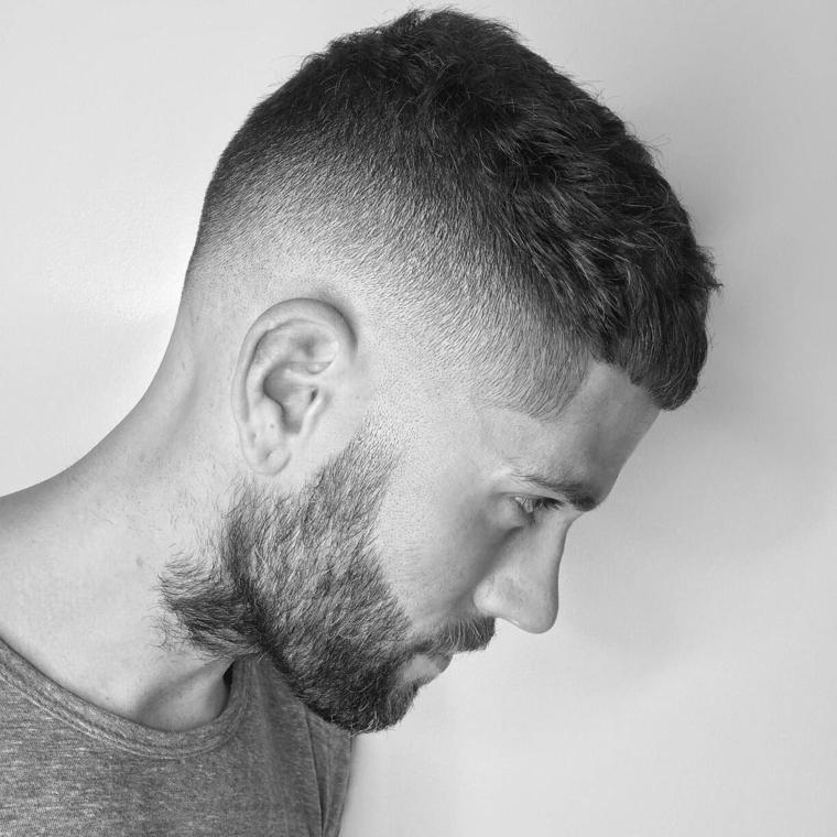 taglio di capelli uomo rasato ai lati lunghi sopra ragazzo con barba