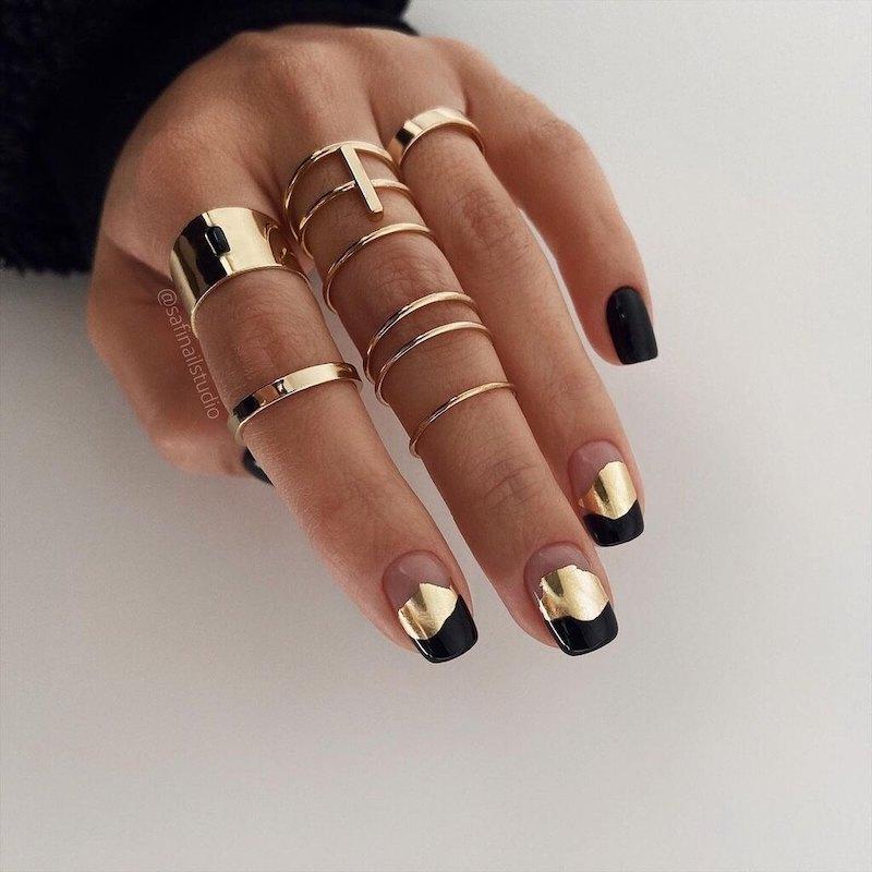 unghie nere opache e oro anelli sulle dita